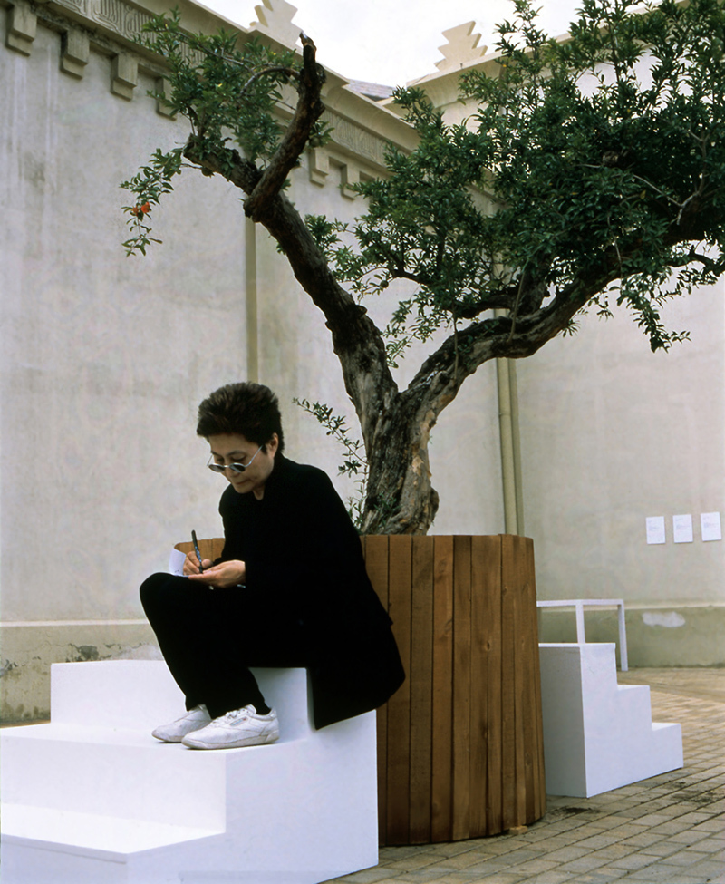 "Yoko Ono, ""Wish Tree,"" 1996/1997, Installation view with artist seated, En Trance – Ex It, Lonja del Pescado, Alicante, Spain (June 23 – July 25, 1997), Photo: Miguel Angel Valero, Courtesy of Yoko Ono"